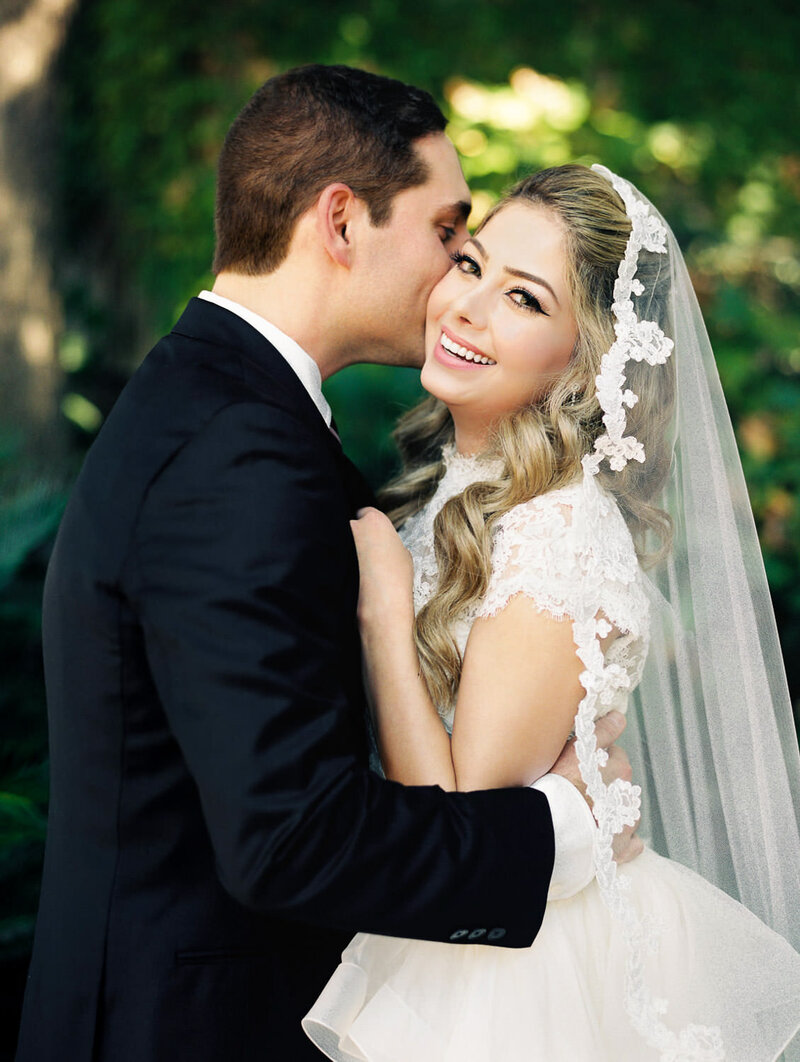 groom embracing bride in wedding dress and veil as she smiles in front of greeery