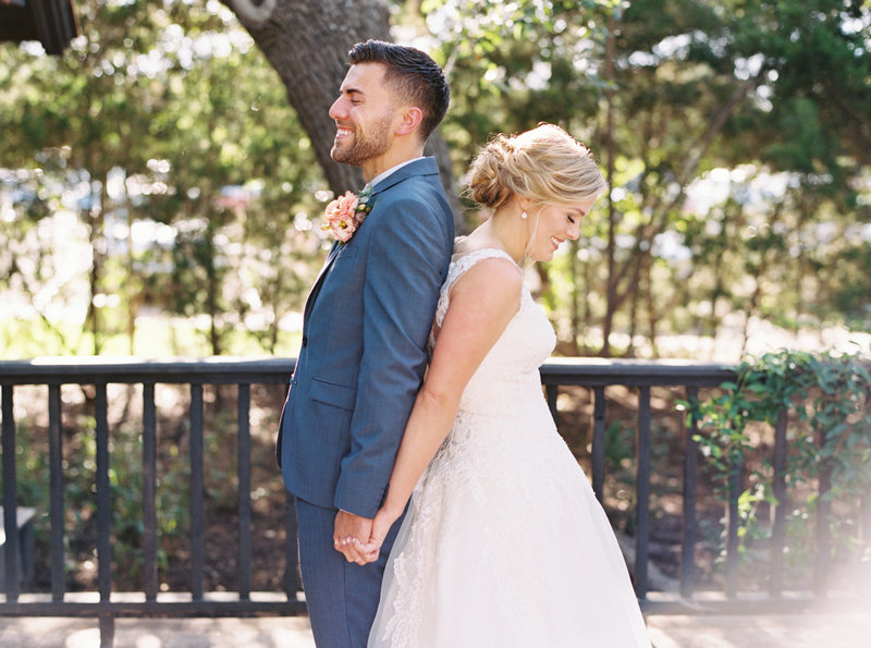 Groom and bride stand back to back smiling