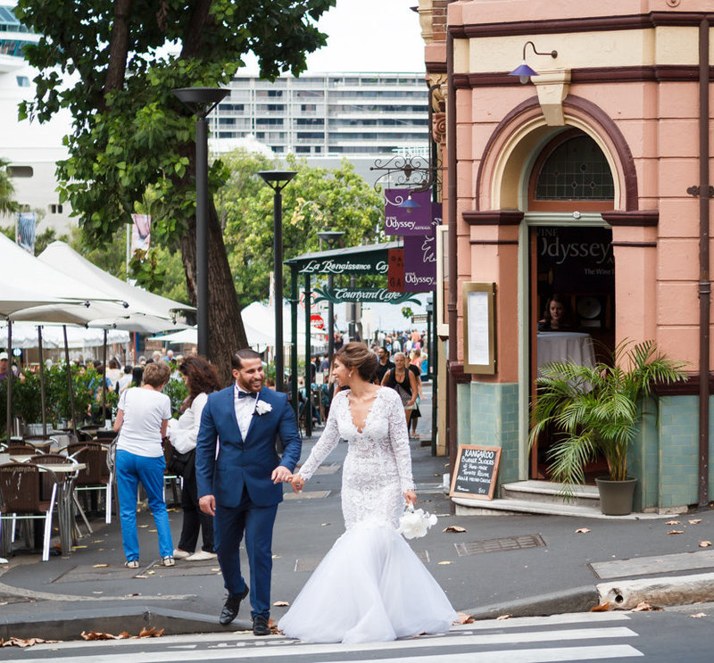 Beautiful wedding day weather as the bride and groom cross the street with their pinky fingers locked