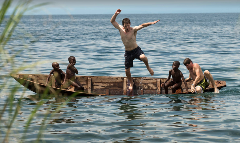 People jumping off a boat for fun in Africa.