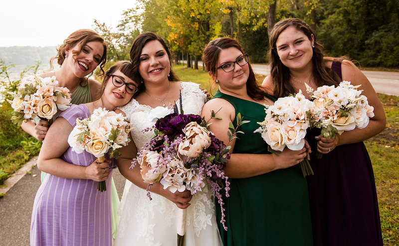 Bride smiles with her bridesmaids  at Presque Isle State Park