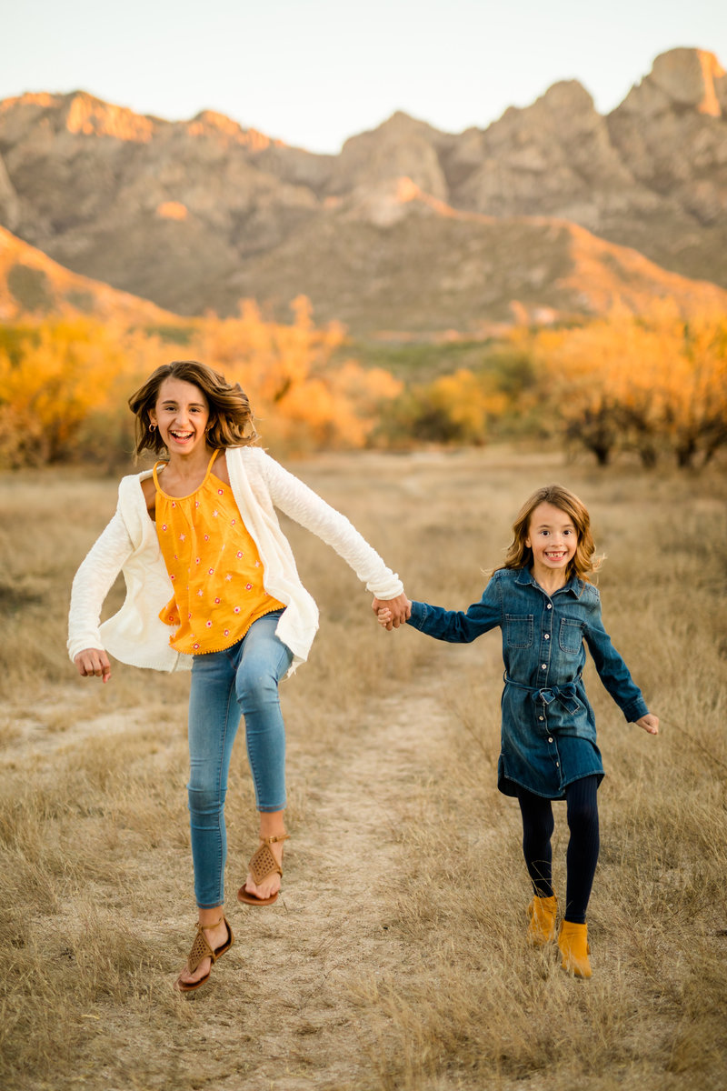 Happy sisters run through the desert wearing yellow during their portrait session in Tucson, Arizona