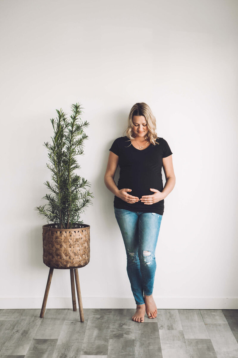 expectant mom in jeans leans on wall by a plant