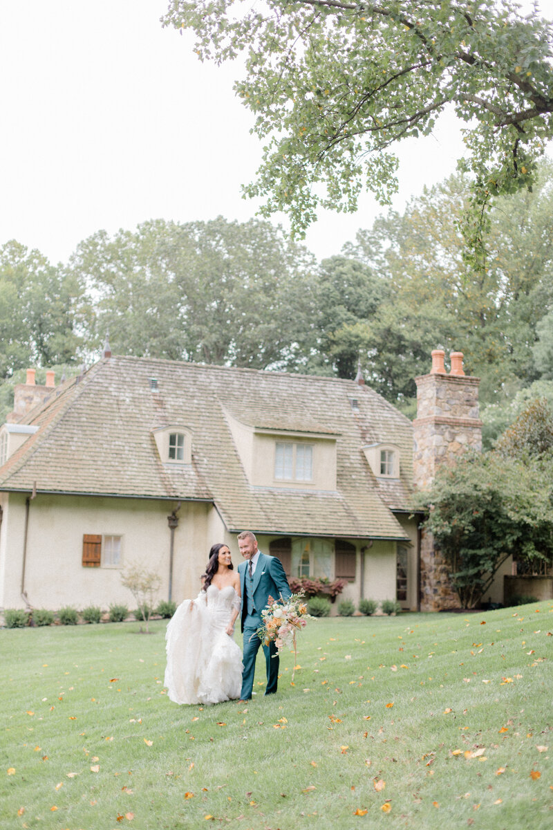 bride and groom walking across lawn at French Inspired Private Estate wedding in charlottesville virginia by costola photography