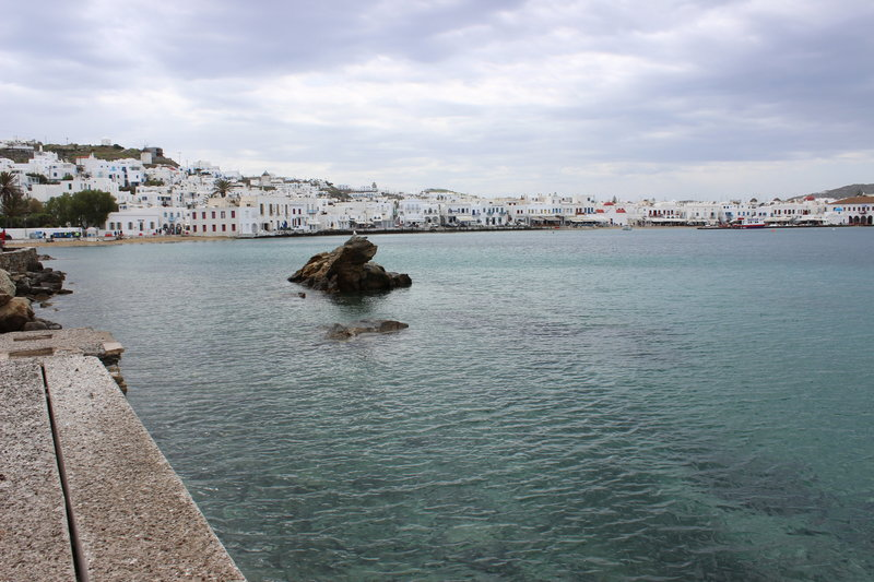 Clear, teal blue water in front of whitewashed buildings on a Greek beach in Mykonos