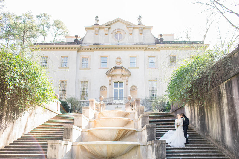bride and groom standing on stairs in front of mansion