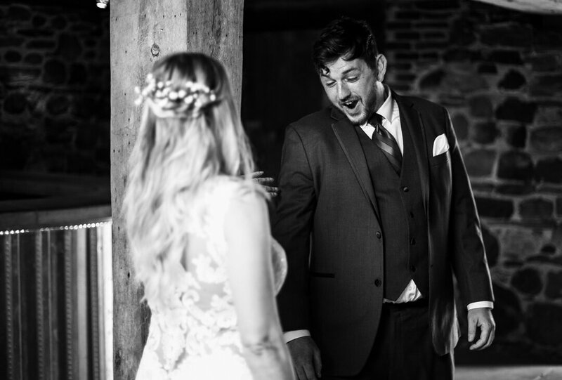 Groom reacts to seeing his bride during first look photos at Quincy Cellars