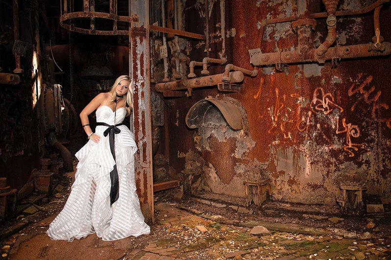 High school senior girl in white tiered dress with black sash leaning on ladder among rusted metal at Carrie Furnace in Pittsburgh, PA
