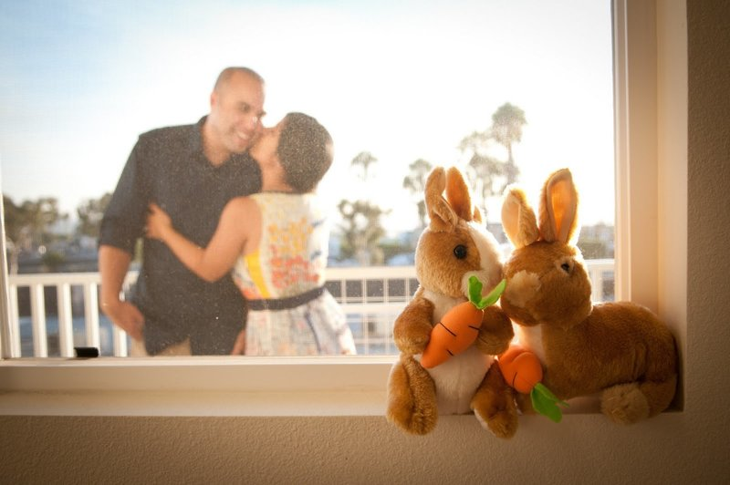 Couple kiss on balcony with stuffed rabbits in the foreground on window sill in focus
