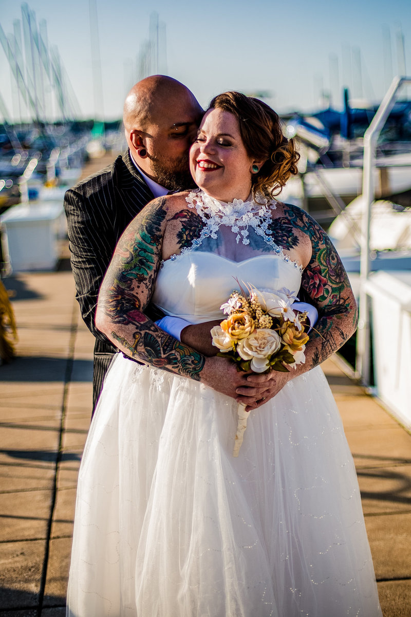 groom whispers in bride's ear as she smiles at the Erie Yacht Club