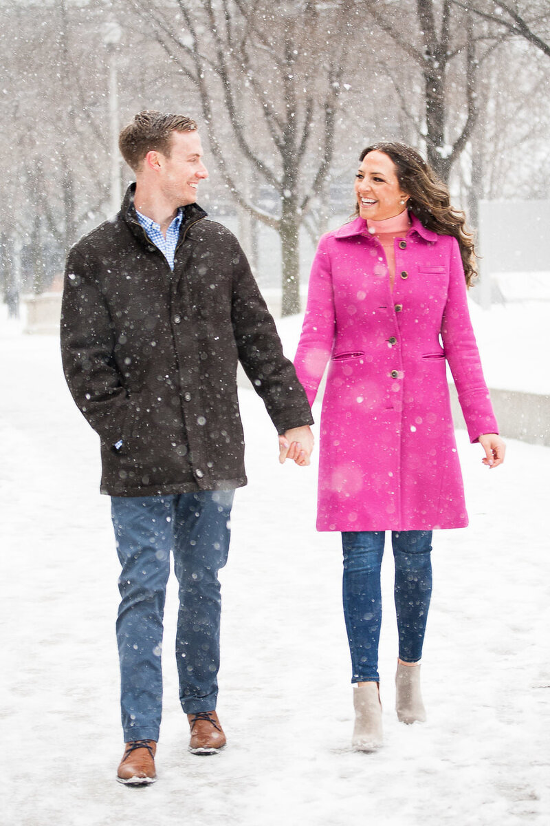 walking holding hands snowy winter engagement session in Millennium Park Chicago