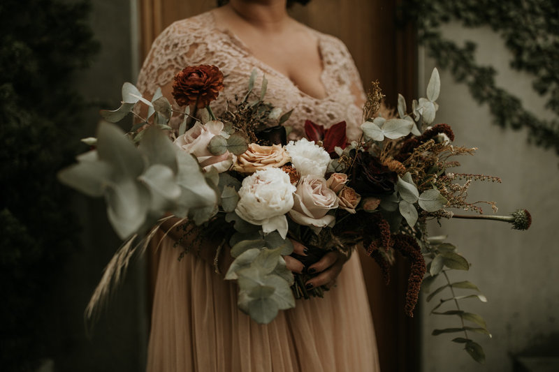 Bride in blush wedding dress with dramatic bridal bouquet of mixed greenery and flowers at this Natural History Museum wedding on New Years Eve