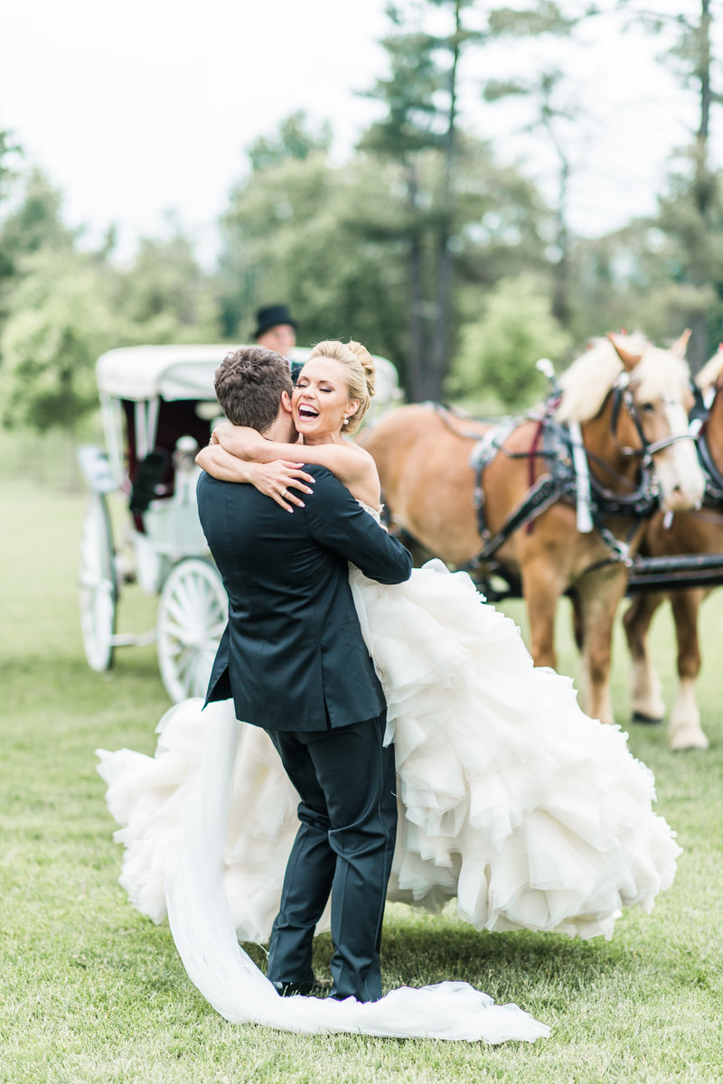 Bride and groom hugging with joy in front of a horse and carriage.