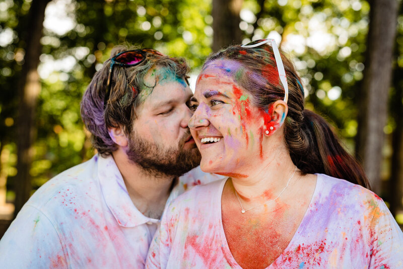 Couple covered in colorful powder smiles and kisses during their engagement photo session