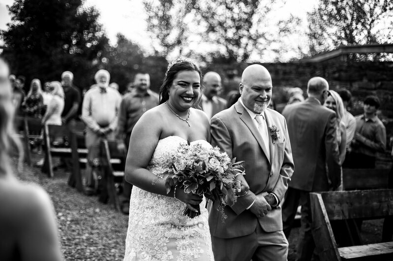 Bride smiles at groom while walking down the aisle at Port Farms