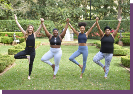 Group of women holding hands while doing a yoga pose