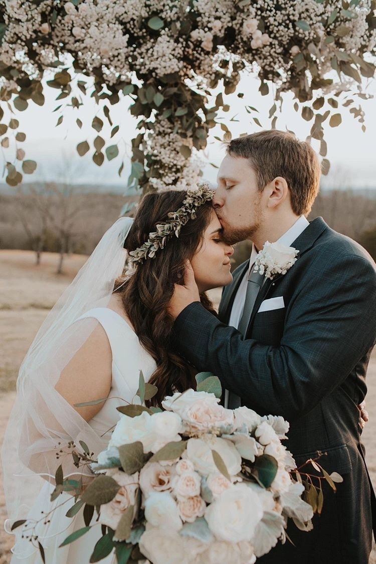 Groom kissing bride in the forehead in front of the ceremony holding a bridal bouquet