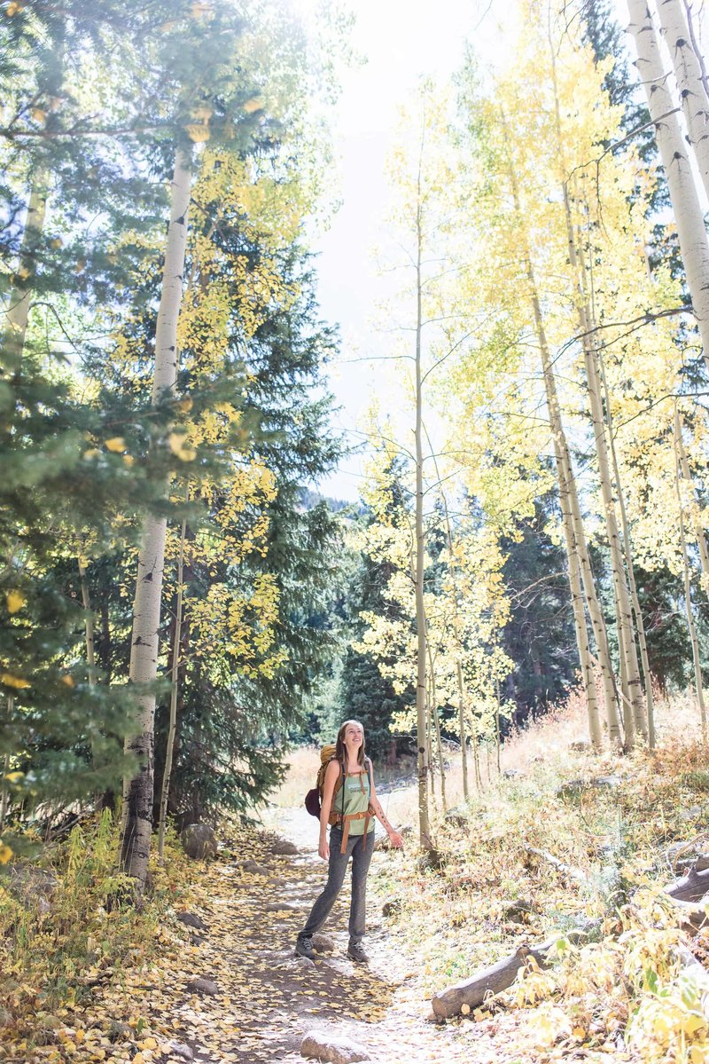 Houston/Austin Texas elopement photographer & planner/guide visits Colorado in peak season. Walking along the trail as aspens fall with the wind.