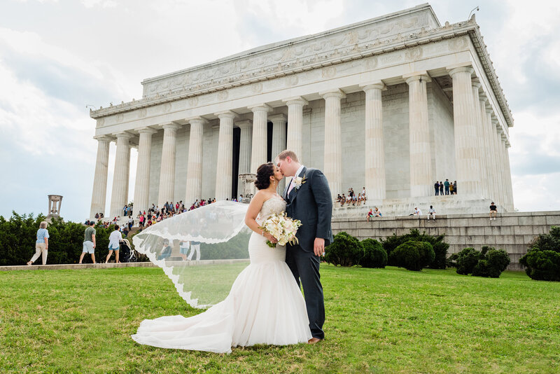 Dramatic photo of a bride and groom kissing in front of the Lincoln Memorial with her veil blowing in the wind on their wedding day. Captured by a DC wedding photographer