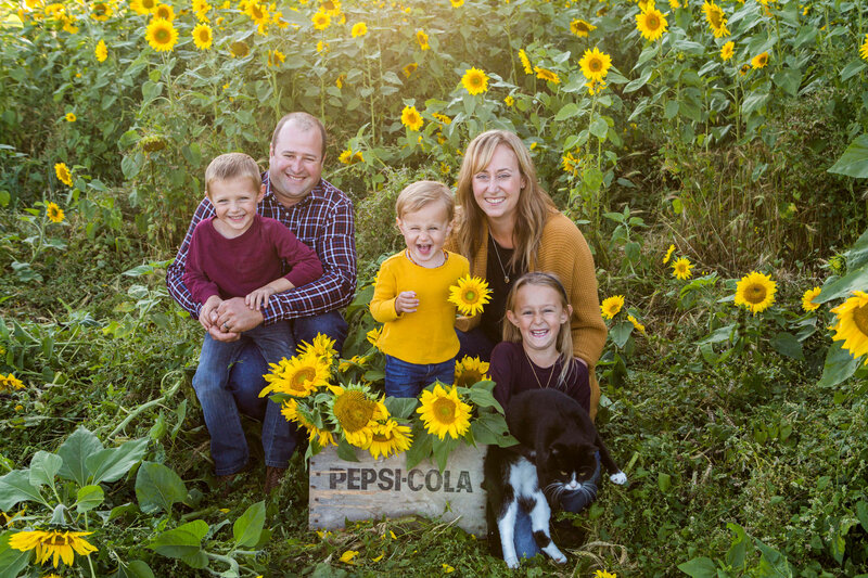 family of 5 in sunflower field
