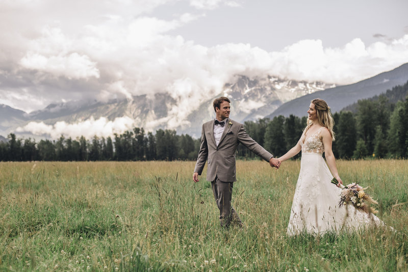 Bride and Groom holding hands walking through a field next to a mountain