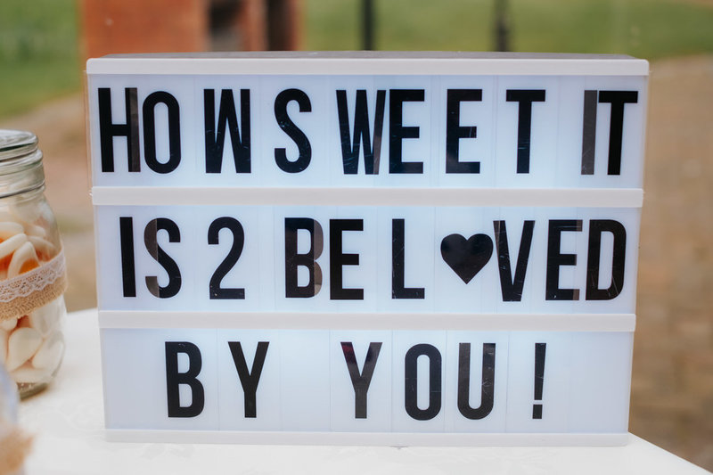 "lightbox sign spelling out ""how sweet it is to be loved by you"""