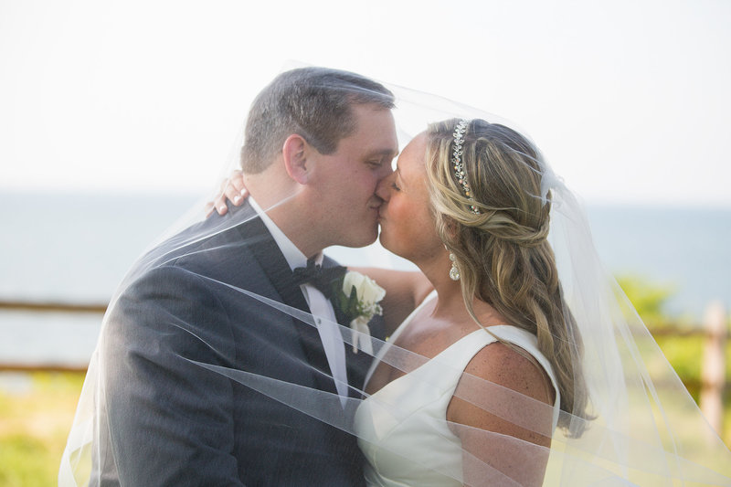 Bride and groom kiss under bride's veil at Lawrence Park golf club