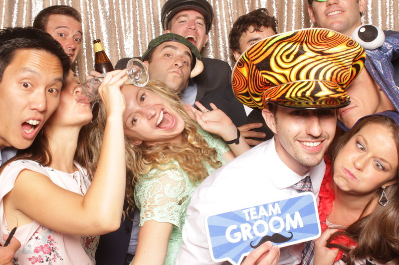 bride and groom with friends in open air photo booth