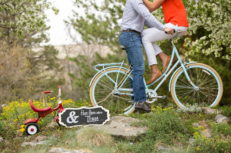 Newly expecting couple pose on a big with a tricycle in the foreground