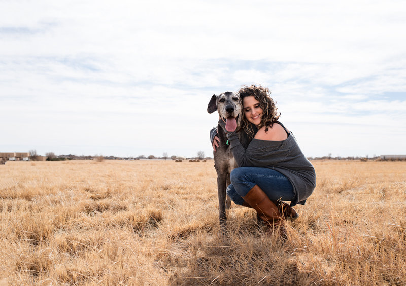 woman in New Mexico field  hugging  dog