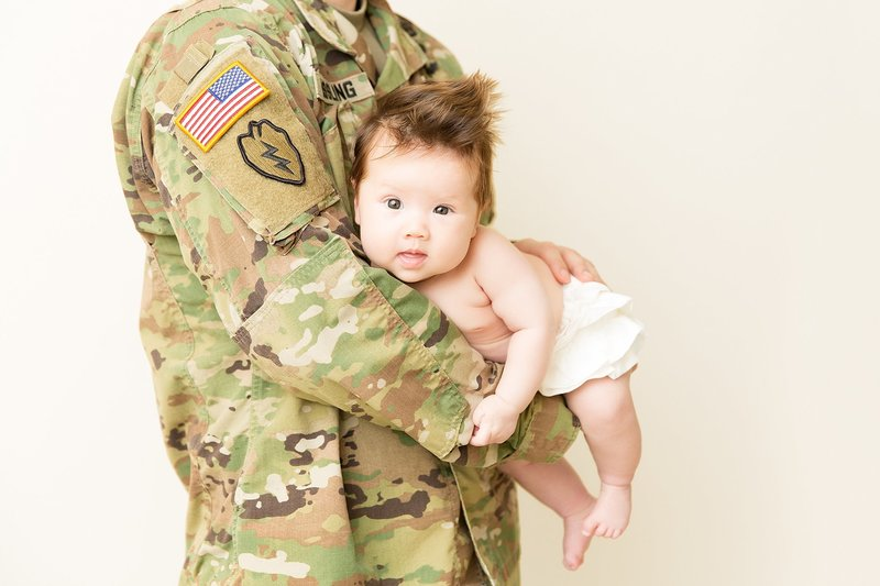 3 month old baby in dads arms with uniform