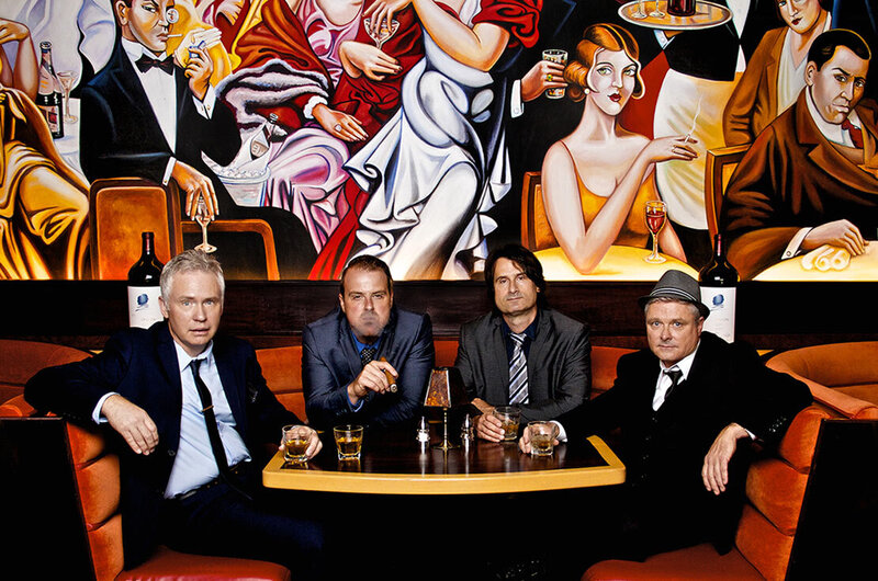 Band photo Nashville The Eventuals four members sitting in restaurant booth art deco mural painted on wall behind them