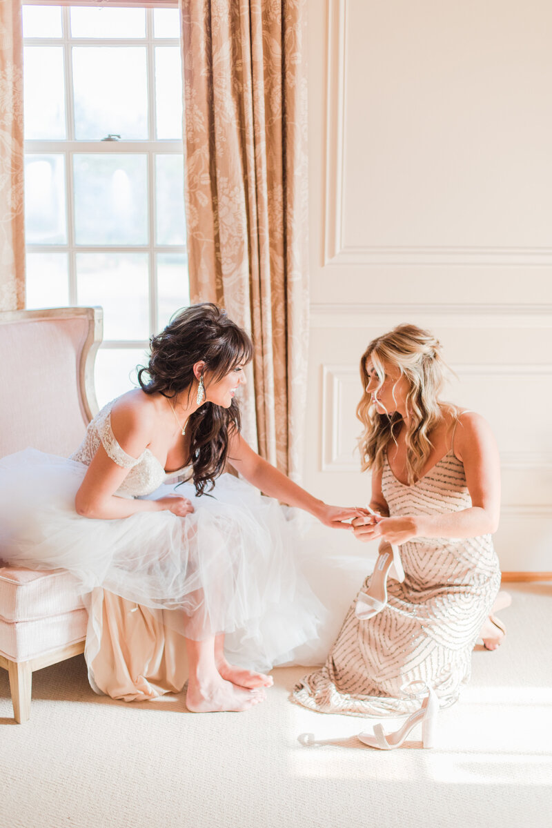 sister helping bride put on shoes at great marsh estate wedding in charlottesville virginia by costola photography