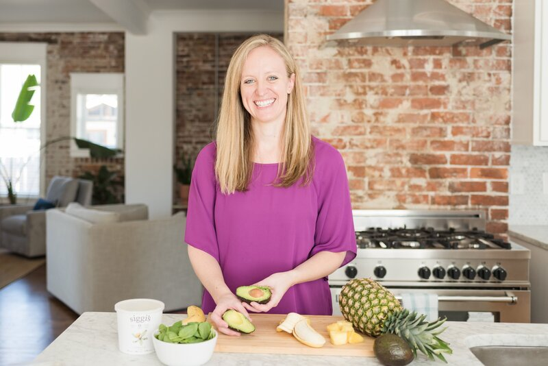 Nutrition coach in purple shirt with fresh bananas, avocados, and pineapples