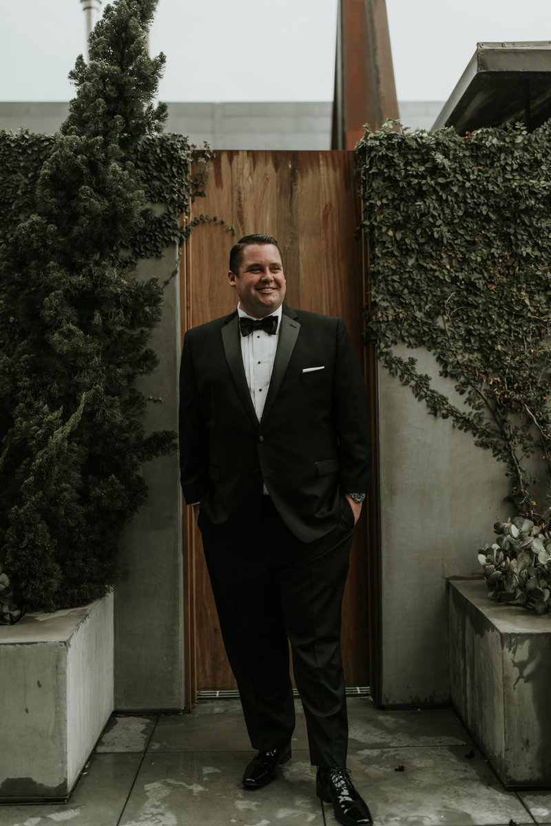 Groom portrait in tuxedo with black bow tie at Natural History Museum in Los Angeles on New Years Eve