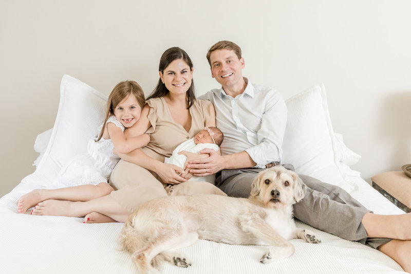 family snuggled on bed with newborn