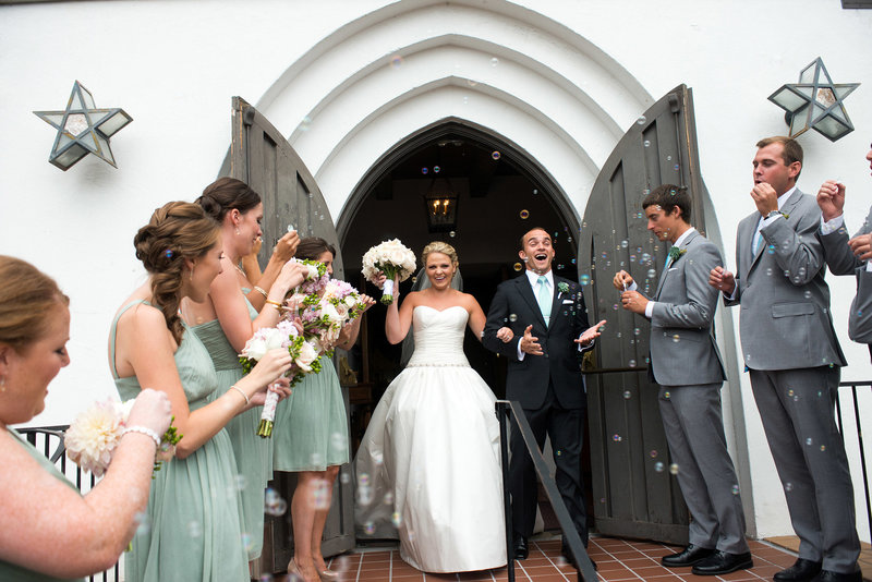 Couple-leaves-church-ceremony-as-wedding-party-blow-bubbles-for-exit