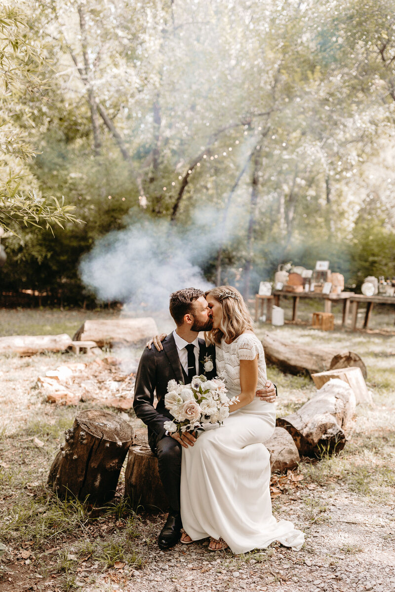 Bride and groom sitting by the fire kissing
