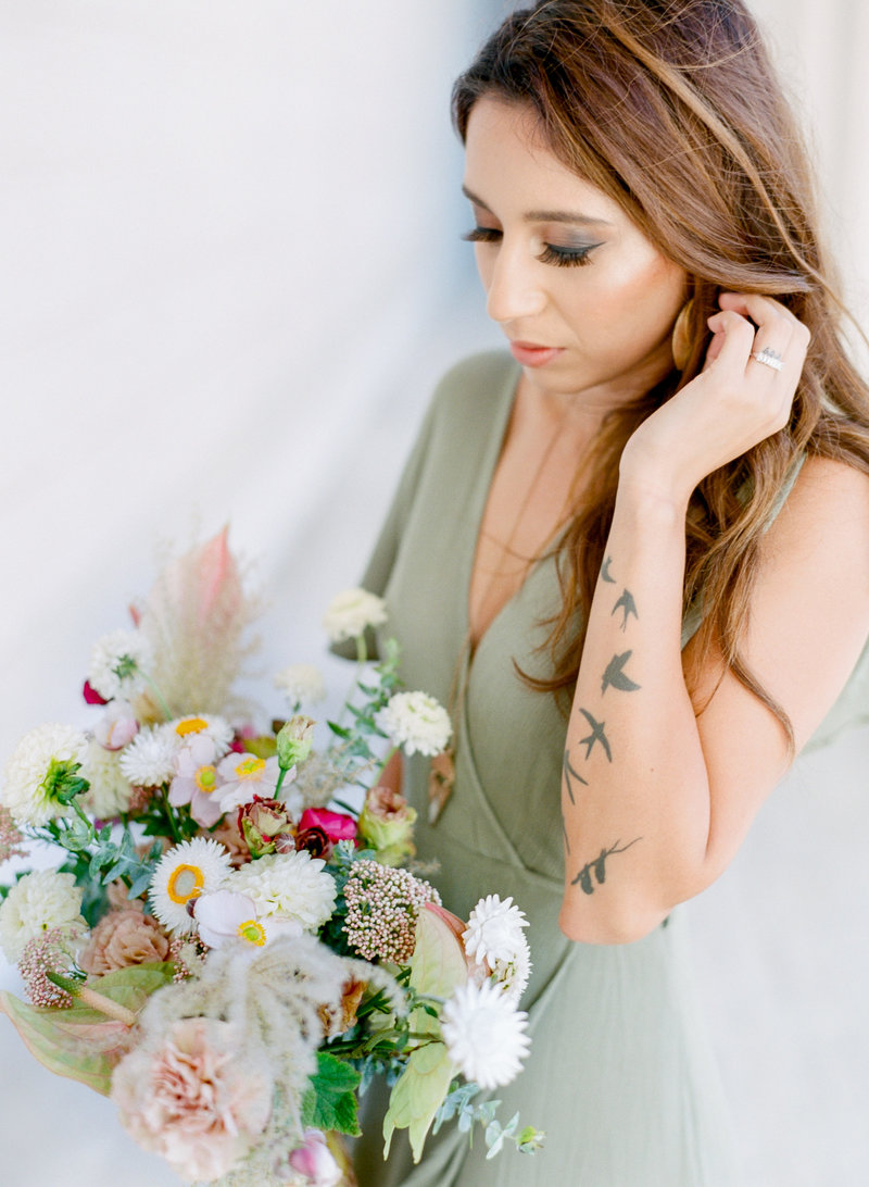 girl with tattoos holding bouquet