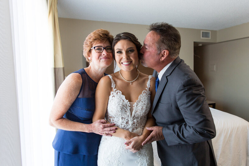 parents kissing bride on wedding day in a downtown detroit wedding
