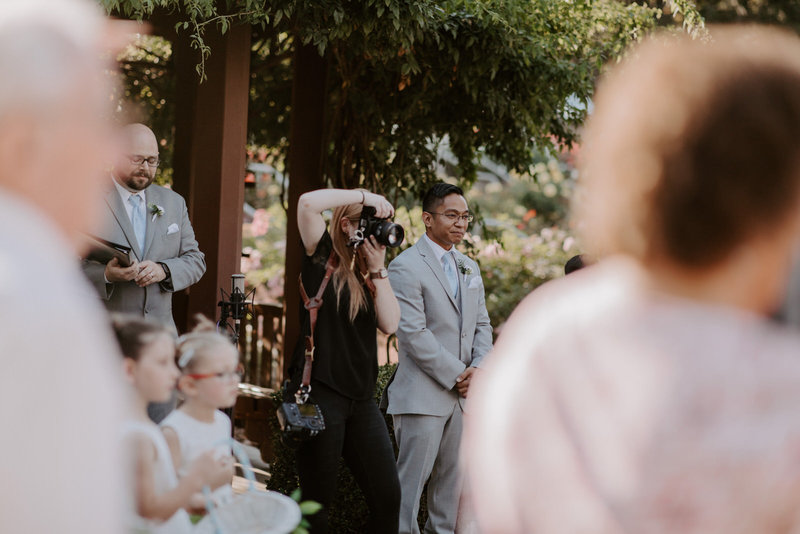 photographer taking picture of bride walking down aisle