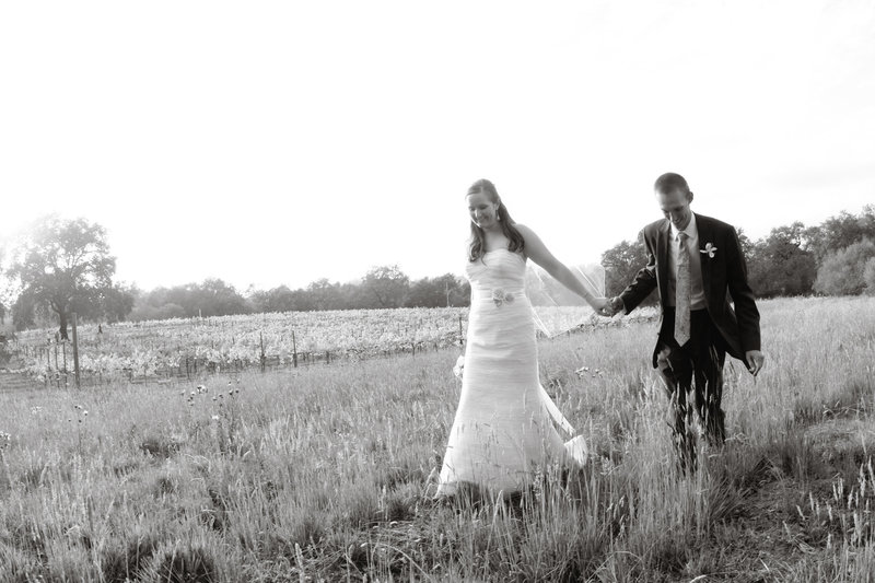 bride and groom walking in field, black and white of bride and groom
