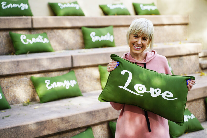 Ashley's Light Spiritual business coach holding pillow that says 'love'.