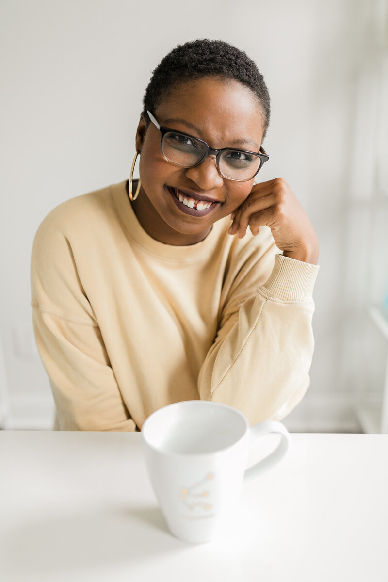 A Black woman wearing a yellow sweater smiling at the camera.