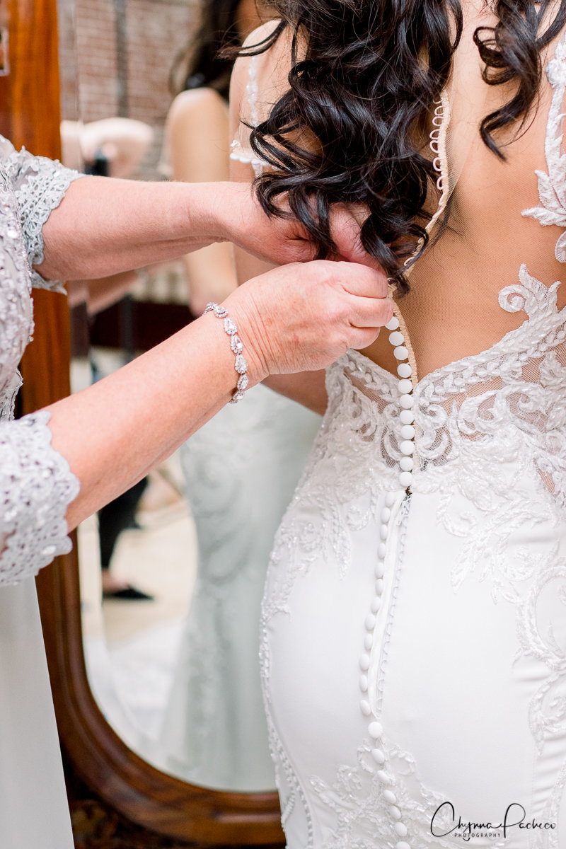 Bride Getting into her Dress | Bella Collina Wedding Photographer