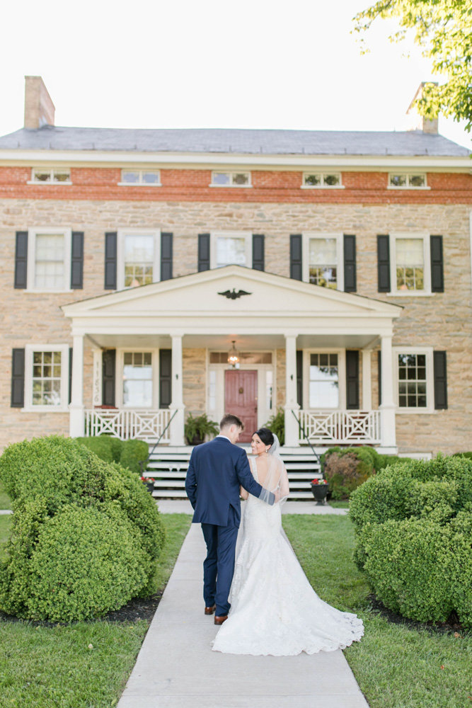 bride and groom walking on sidewalk at springfield manor winery and distillery wedding by costola photography