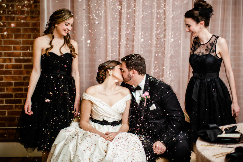 Woman in wedding dress kissing man in black tux while bridesmaids in black toss confetti smiling