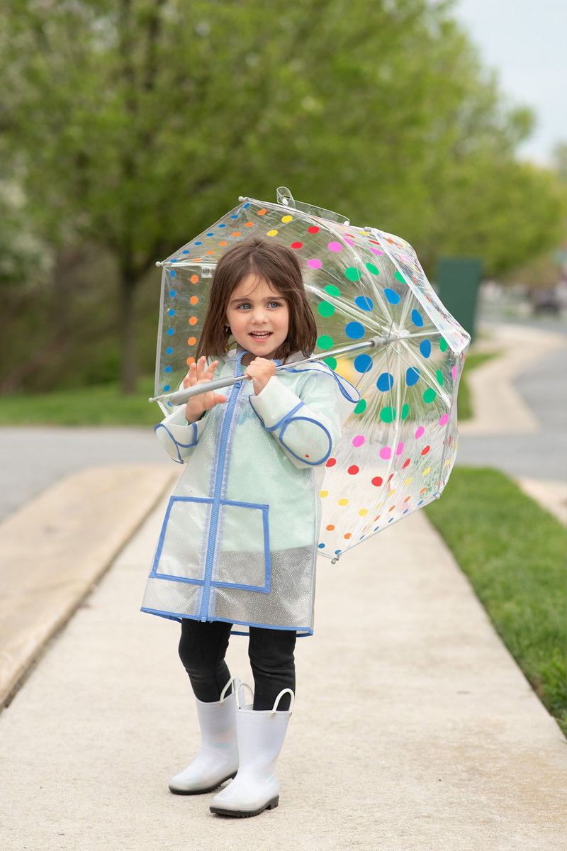 Little girl standing with rain coat and umbrella