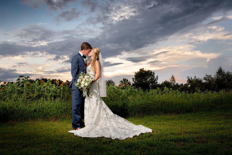 bride and groom kiss in front of a brilliant sky at Wildberry Farm
