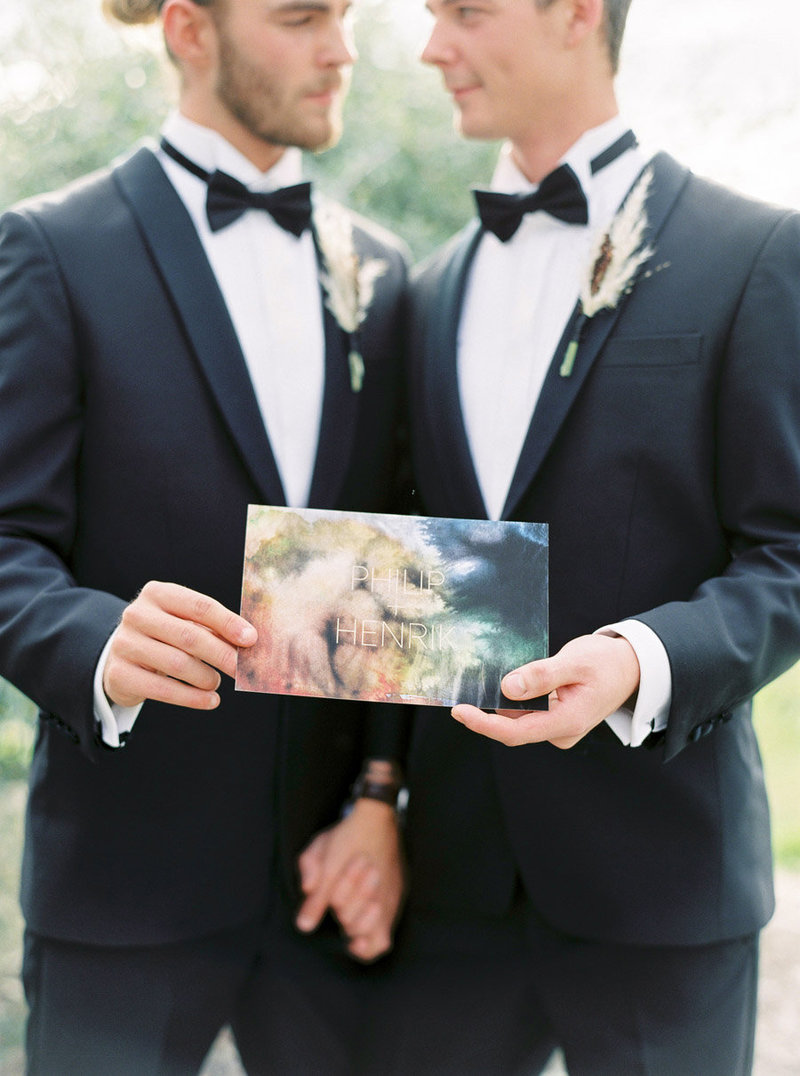 010-groom-and-groom-holding-a-set-of-wedding-invites